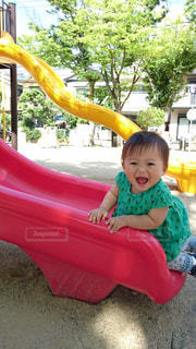 小さな子供が滑り台の上に座っているの写真・画像素材[2116065]