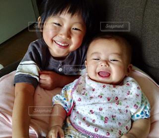 赤ん坊を抱いている小さな女の子の写真・画像素材[2374067]