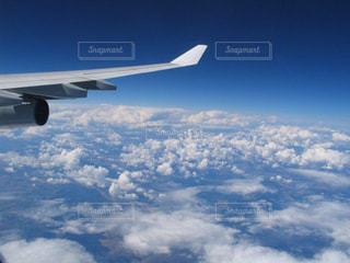 青い空を飛んでいる飛行機の写真・画像素材[1587361]
