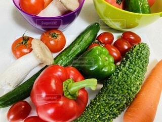 食べ物,風景,夏,マイホーム,屋内,緑,赤,カラフル,景色,テーブル,まな板,トマト,野菜,食品,人参,ピーマン,健康,ゴーヤ,プチトマト,食材,リフレッシュ,パプリカ,夏野菜,フレッシュ,生野菜,ベジタブル,きのこ,栄養,きゅうり,エリンギ,ボウル,インスタ映え