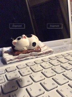 コンピューターのマウス、キーボードの横に座っているデスクの写真・画像素材[1631734]