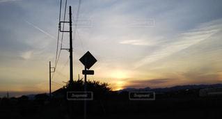 空,夕日,屋外,太陽,雲,晴天,夕焼け,夕方,田舎,シルエット,日没,電柱,電線,逆光,住宅,温室,飛行機雲,夕陽,景観,住宅地,交通標識,田舎の風景,高い雲,薄雲,ミルクティー色,上空の雲,天気下り坂