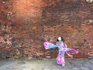 れんが造りの建物の前に立っている女の子の写真・画像素材[1522783]
