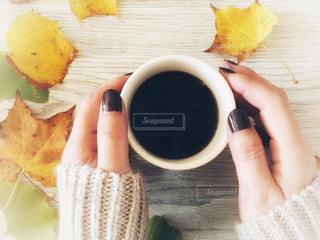 女性の手とコーヒーのカップの写真・画像素材[1548705]