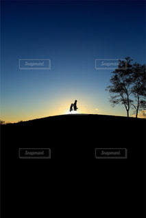 丘の上で夕日をバックに、親子でジャンプの写真・画像素材[1591487]