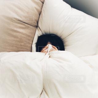 ベッドの上で横になっている人の写真・画像素材[1625139]