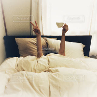 白いシーツのベッドで寝る女性の写真・画像素材[1625147]