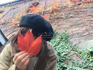 ベレー帽をかぶっている女性がもっている紅葉した葉っぱの写真・画像素材[1636886]
