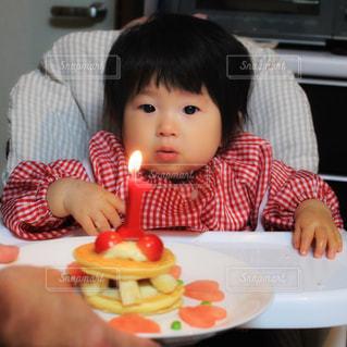 バースデー ケーキでテーブルに座っている少女の写真・画像素材[1667460]