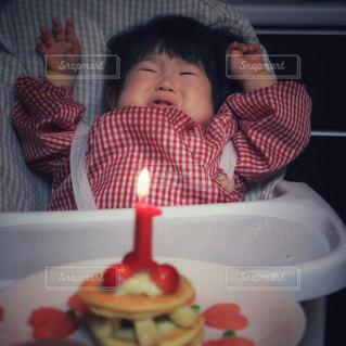 お誕生日ケーキを前にテーブルに座っている小さな子供の写真・画像素材[1667472]