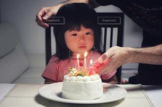 キャンドルとバースデー ケーキの前に座っている少女の写真・画像素材[1667500]