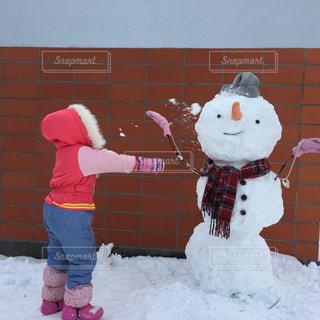雪だるまと雪合戦をする女の子の写真・画像素材[1714842]