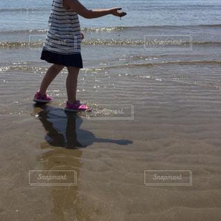 ビーチの砂の上に立っている少女の写真・画像素材[1798742]