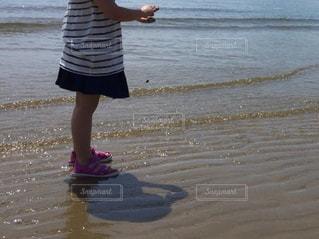 ビーチの砂の上に立っている少女の写真・画像素材[1798756]
