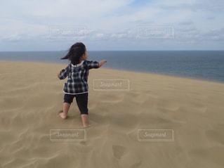 水のボディの隣に立っている小さな女の子の写真・画像素材[2096805]
