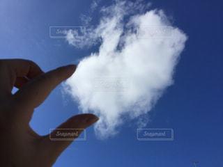 青い曇り空を持つ手の写真・画像素材[2417135]