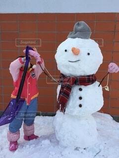 ピンクのスノースーツを着た女の子と雪だるまの写真・画像素材[4169614]