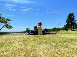 キャンプ場の芝生の上に座っている親子の写真・画像素材[4596177]