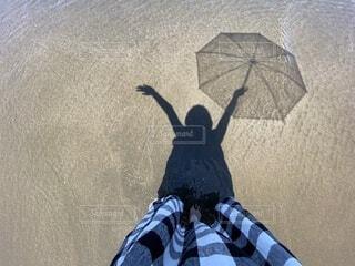 波打ち際で傘を持っている女性の影の写真・画像素材[4641208]