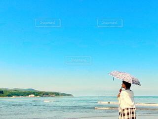 砂浜で日傘を持っているワンピース姿の女性の写真・画像素材[4641252]