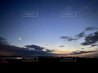 地平線と夕暮れの月の写真・画像素材[4752319]