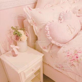 ベッドの上のピンクの花の写真・画像素材[1477185]