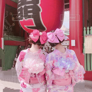 店の前のピンクのドレスの立っている女の子の写真・画像素材[1477418]