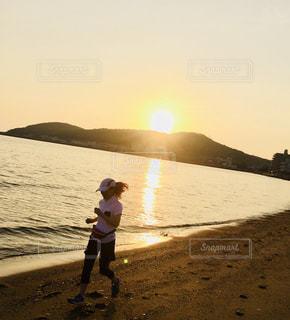 夕陽を眺め眺めながら海岸でランニングの写真・画像素材[1508072]