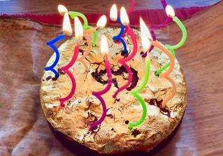 木製テーブルの上に座っているバースデー ケーキの写真・画像素材[1548222]