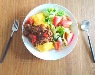 テーブルの上の皿の上にオムライスとサラダの写真・画像素材[1563420]