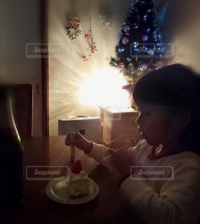灯りを消してクリスマスケーキを食べる女の子の写真・画像素材[1669298]