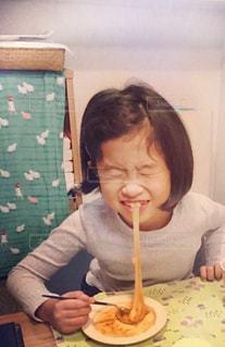 食事のテーブルに座ってお餅を食べている子供の写真・画像素材[1669496]