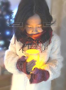 クリスマスツリーの前でキャンドル風の照明を抱える女の子の写真・画像素材[1672915]