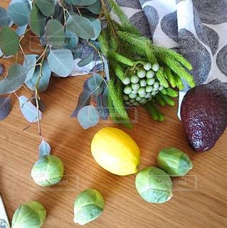 木製テーブルの上にレモンとアボカドと芽キャベツとユーカリの写真・画像素材[1763736]