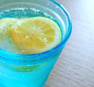 水で満たされたブルーのグラスにレモンの写真・画像素材[1763779]