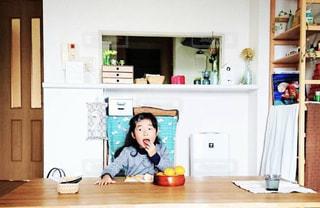 リビングで机に座ってみかんを食べる女の子の写真・画像素材[1798216]