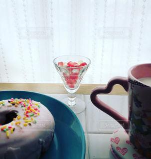窓辺のタイルテーブルの上にドーナツとミルクの入ったハートのカップとピンクのグミの写真・画像素材[1813771]