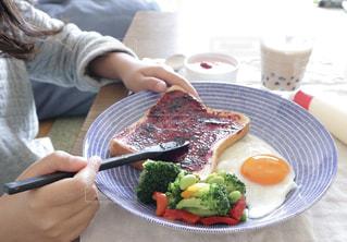 目玉焼きとサラダとトーストのワンプレートのトーストにジャムを塗っている女の子の手の写真・画像素材[1855453]