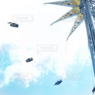 遊園地にて青空の下空中ブランコのアトラクションで楽しむグループの写真・画像素材[1910127]