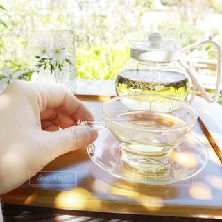 コップ一杯のハーブティーをテーブルに持っている人のクローズアップの写真・画像素材[2140816]