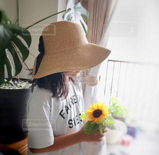麦わら帽子を被り手にひまわりを持った女の子 すっかり夏仕様。この格好で駄菓子屋さんにお友達と👒🌻の写真・画像素材[2156244]