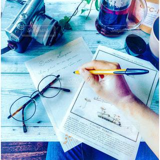 テーブルの上に置かれた文房具と手紙を書く人とカメラの写真・画像素材[2263494]