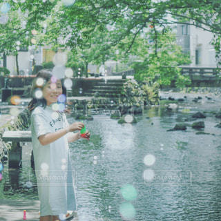 川の隣に立っている人の写真・画像素材[2435239]