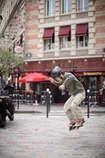 うちの前の広場でローラーブレードでジャンプを楽しむ男の子の写真・画像素材[1506795]
