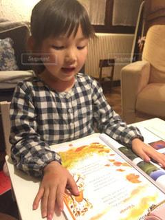 テーブルに座ってお勉強するの女の子の写真・画像素材[1547483]