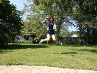 庭で高くジャンプをする女の子の写真・画像素材[1599414]