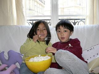 ソファーでポップコーンを食べながらビデオ鑑賞の写真・画像素材[1621754]