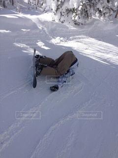 雪をスノーボードに乗る男覆われた斜面の写真・画像素材[1507808]