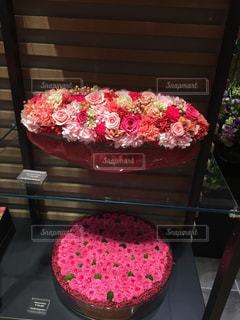 木製テーブルの上に座っているピンクのケーキの写真・画像素材[1565445]