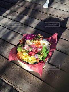 木製テーブルの上に座っている花の花瓶の写真・画像素材[1565484]